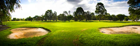 courses: Picturesque Green Grassy Golf Course Landscape Panorama Complete With Two Sand Bunkers Stock Photo