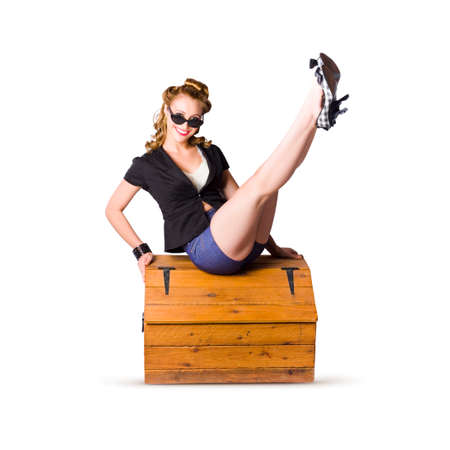 hinged: A smiling glamorous pin up woman wearing black top and blue shorts, seated with legs in the air on a pine trunk isolated on white background Stock Photo
