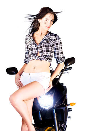 handlebars: Sexy young woman in shorts posing on the handlebars of a motorbike with its headlamp shining Stock Photo