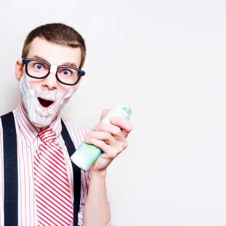 sensitive skin: Portrait Of A Surprised Man Wearing Nerd Glasses Holding Shaving Cream With Foam Beard In A Depiction Of Sensitive Skin, Studio Background