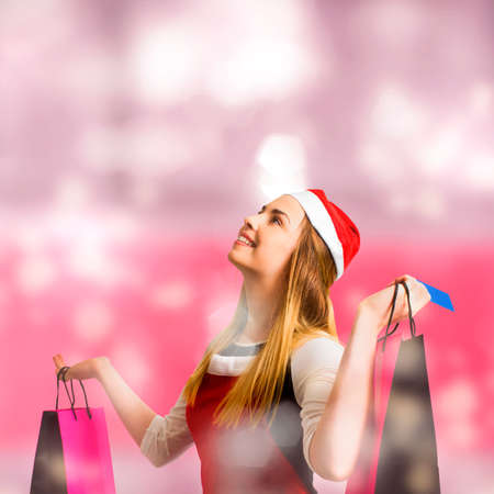 retail store: Shopping centre concept on a retail christmas holiday woman holding credit card while looking up with store bags. Copyspace shopper girl