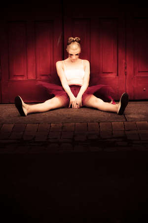 glooming: Locked Out Dancer Sits In Front Of A Big Red Door With Head Hanging Low In A Sad And Sorrowful Portrait Of Failure Loss And Suffering, Text Copyspace On Black Stock Photo