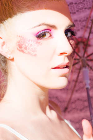 lacey: Creative Storm Concept With A Woman In Pretty And Glamorous Lacey Styled Make Up Holding A Pink Umbrella In The Summer Sun Stock Photo