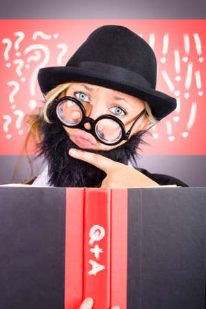 nutty: Thinking nutty professor holding text book with Q and A on the spine in a question and answer conceptual Stock Photo