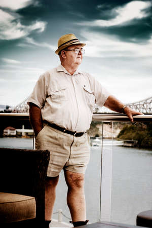 portly: Elderly Retired Man In Shorts Standing On The Deck Of His Luxury Waterfront House Overlooking The Sea In A Financial Planning For A Wealthy Retirement Concept Stock Photo