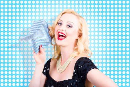 duties: Beautiful happy woman housewife holding blue polka dot washing cloth. Doing daily house work duties around a retro home Stock Photo
