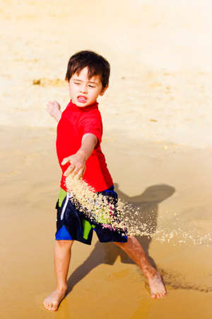fling: Happy young Asian boy on vacation playing in his shorts on the beach throwing wet sand in a motion action capture