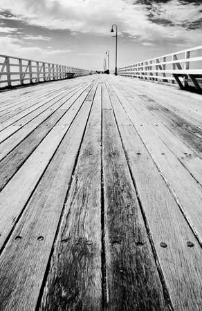 emptiness: Emptiness Fills My Steps, While Vertical Lines Of Solitude Stretch The Void, On The Boardwalk Of Distance Stock Photo
