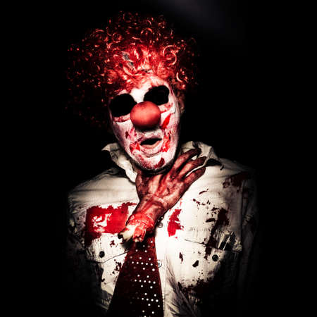 Evil Portrait Of A Creepy Clown Getting Chocked By A Dead Amputated Hand On Dark Studio Background Stock Photo