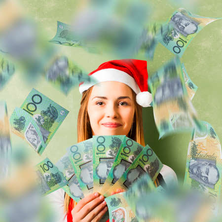 creative money: Creative green cash photo on a christmas woman celebrating a win with Australian 100 Dollar money fan. Savings in Australia Stock Photo
