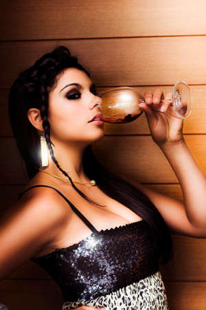 party outfit: Sexy attractive woman in evening party outfit drinking from a wine glass at a nightclub with a wooden board background Stock Photo