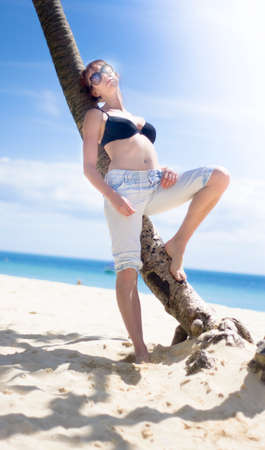 bikini top: Attractive Young Woman With Bikini Top Leaning Against Palm Tree Trunk On Sandy Beach In Tropical Island Paradise Stock Photo