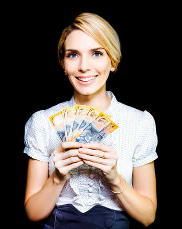 money hand: Attractive blonde business woman holding a cash bonanza of banknotes in her hand which she has won in an unexpected windfall and for which she is truly appreciative Stock Photo