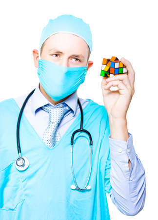 medical cure: Frustrated Male Medical Surgeon Holding A Jigsaw Cube Searching For A Undiagnosed Cure In A Depiction Of A Doctor Problem Solving A Medical Complication Stock Photo