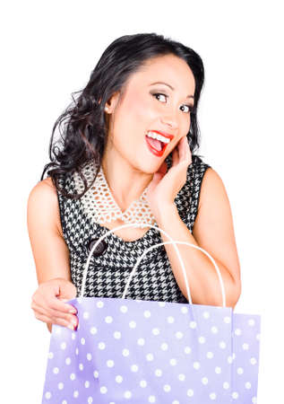 astounded: Good looking Asian girl expressing excitement while looking into a dotted purple shop bag. Shopping Sales Stock Photo