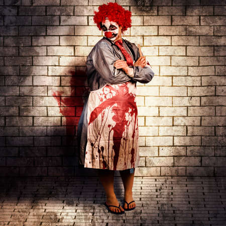 Murderous monster clown standing in full length on brick illustration background with blood stained apron. Killing medical practice