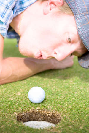 desperately: Desperately Wanting A Hole In One Off A Four Par A Golfer Puffs On A Golf Ball To Motion It Into The Hole In A Funny Golfing Cheat Concept Stock Photo