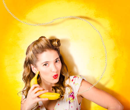 olden: Comic photo of a retro pin-up girl with olden day hair rolls making funny surprise expression when talking bananas through fruit phone on yellow grunge wall.  Stock Photo