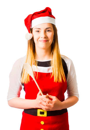 hospitality staff: Adorable seasonal portrait of a blond christmas woman holding wooden spoon in santa outfit. Sweet kitchen helper