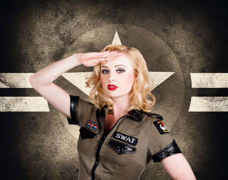Beautiful pin-up girl in classic military uniform posing a salute with wavy short blond hair style on grunge star background.  Vintage and retro fashion style