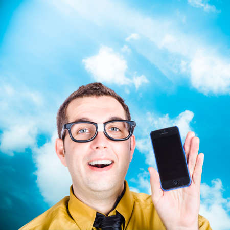 savvy: Smiling technology savvy businessman displaying blank smart mobile phone screen. Outdoors background