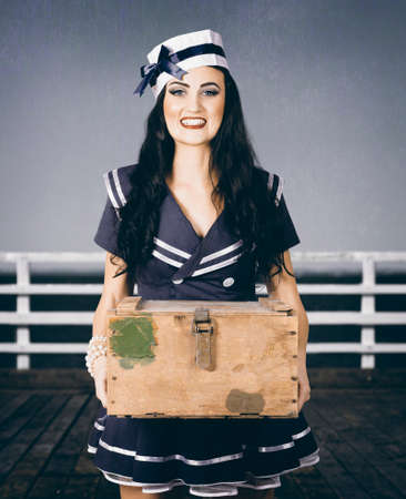 sailor girl: Faded photo of a beautiful retro sailor girl smiling in vintage fashion style holding military ammo box. Tour of duty