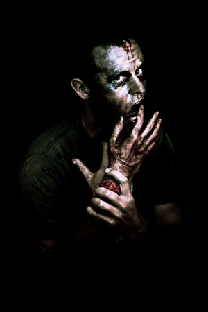 creepy hand: A decaying zombie feeds on a severed bloody human hand in the darkness of midnight in a deadly midnight snack conceptual Stock Photo