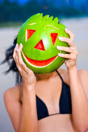 obscuring: Bikini Woman At Beach Holding A Carved Happy Smiling Watermelon In Front Of Her Face At The Beach Stock Photo