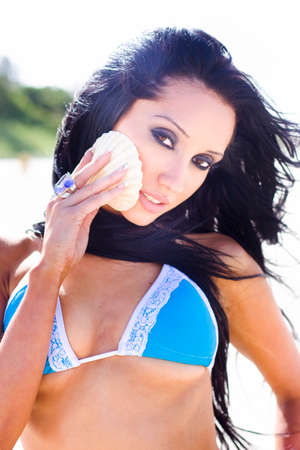 sightseeing tour: Beautiful Attractive Woman Holds Up A Sea Shell To Her Face When Exploring The Beach  In A Beach Sightseeing Tour Concept Stock Photo