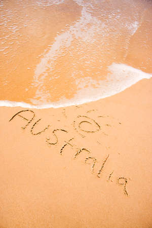 short wave: A Wave Rolls Up Just Short Of 'Australia' Hand Written In The Sand