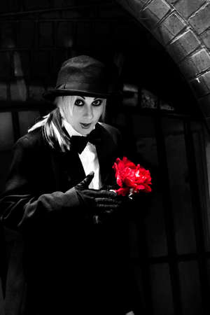 trickster: A Mysterious Black Magician Holds A Surprise Flower Gift In A Magic Trick Performed On A Darkened Street Corner Stock Photo