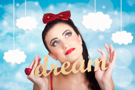 succeed: Attractive young pinup girl looking up to the clouds of inspiration with the words dream in hand. Dreaming to achieve to succeed