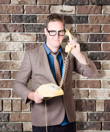 Chatter: Humorous male nerd engaging in business chatter on phone with discussions of retro revival. Brick wall background Stock Photo