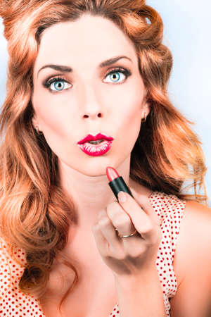 red hair beauty: Vintage fashion portrait of a cute 50s pin up girl with amazing red hair style applying lipstick makeup. Retro beauty model