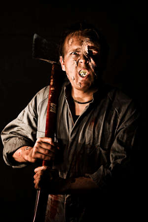 maniacal: A killer zombie holding an axe in the darkness with decaying flesh on his face and mouth, conceptual horror for halloween