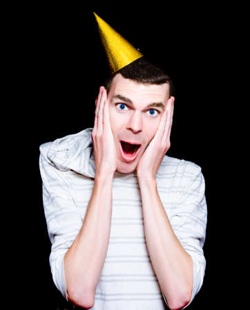 surprise party: Shocked Looking Young Man With Party Hat In A Surprise Birthday Concept Isolated On Black Background