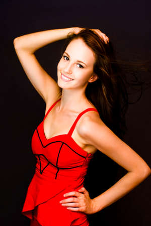 enchanting: Enchanting lively young woman in a sexy red dress with a beaming radiant smile. Stock Photo