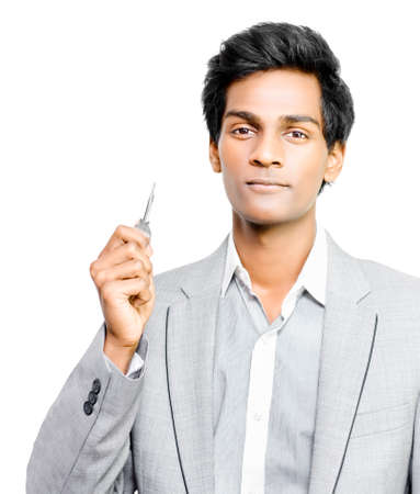 ownership and control: Smart young Asian businessman holding the key to unlock greater opportunities on the path to success or to signify his acceptance into a new partnership, ownership and wealth Stock Photo