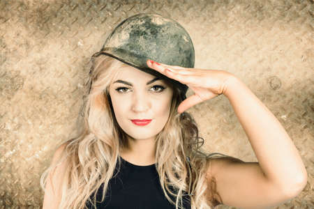 new recruit: Old style portrait of an enthusiastic blond army pin-up girl wearing grunge helmet saluting for enrolment at a new recruit office. Sign up draft Stock Photo