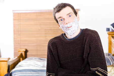 male grooming: Funny man standing indoors at home smiling with shaving cream foam beard. Male skincare and grooming concept