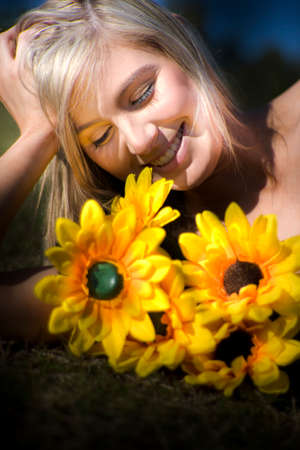 blond haired: Portrait Of Happy Young Blond Haired Woman With Blooming Sunflowers Outdoors