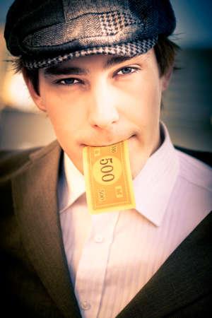 hombre comiendo: El gasto grande hombre corroyendo sus ganancias en efectivo al poner un 500 notas del dólar en su boca en señal de cuentas, el consumo y la deuda financiera