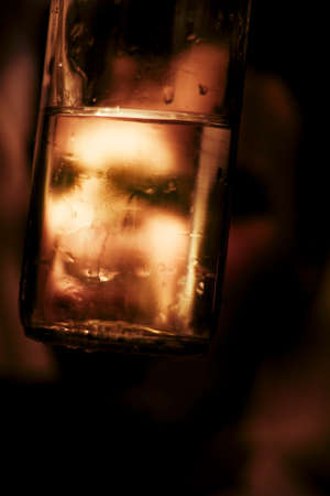 Negative Concept On The Effects Of Alcohol With The Focus On The Face Of A Unhappy Drunk Man Through The Glass Bottle He Is Consuming At A Party