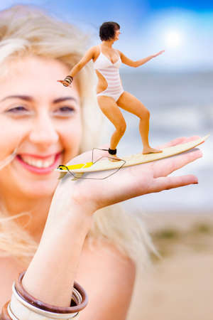 curio: Surf Water Sport Image Of A Happy Blond Beach Bather Woman Holding Out Her Hand With Her Friend Hanging 10 While Riding A Wave In A Comical Hand Surfer Concept Stock Photo