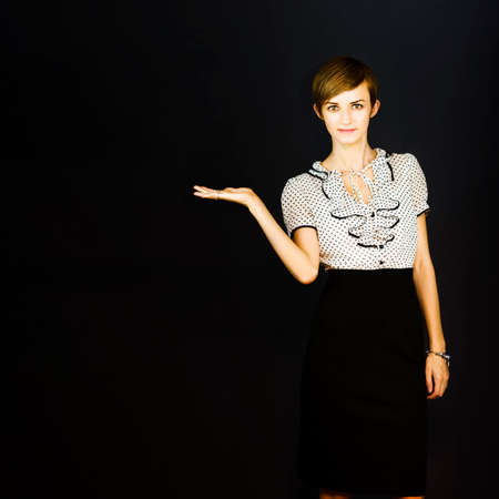 frilly: Pretty pert young saleswoman in a frilly blouse standing with her hand open palm upwards for placement of your product and advertising on a dark background