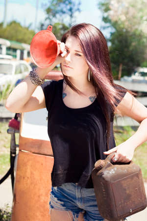 environmentalist: Female Environmentalist Stares Through A Petrol Funnel To Glimpse The Forecast Ahead On The Future Of Oil