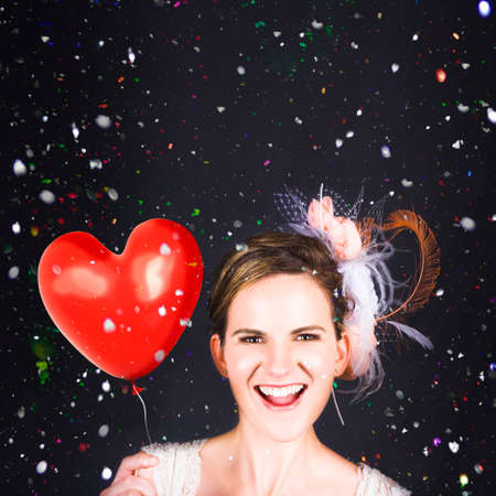 struck: Creative Portrait Of A Love Struck Bride Holding Love Heart Balloon While Walking Through Falling Colorful Confetti During A Wedding Celebration