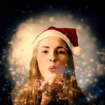 christmas woman: Fine art Christmas portrait of a lovely young blond woman blowing magic snow dust in an expression of xmas love. Seasons greetings
