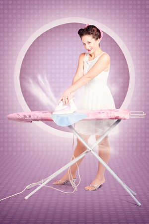 50s fashion: Full body retro pin up lady doing ironing choirs with smoking hot iron in 50s fashion style on purple polka dot background