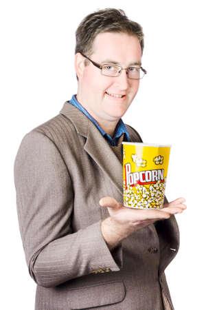 hombre comiendo: Retrato de hombre de negocios Con Palomitas cubo aislado en el fondo blanco Foto de archivo